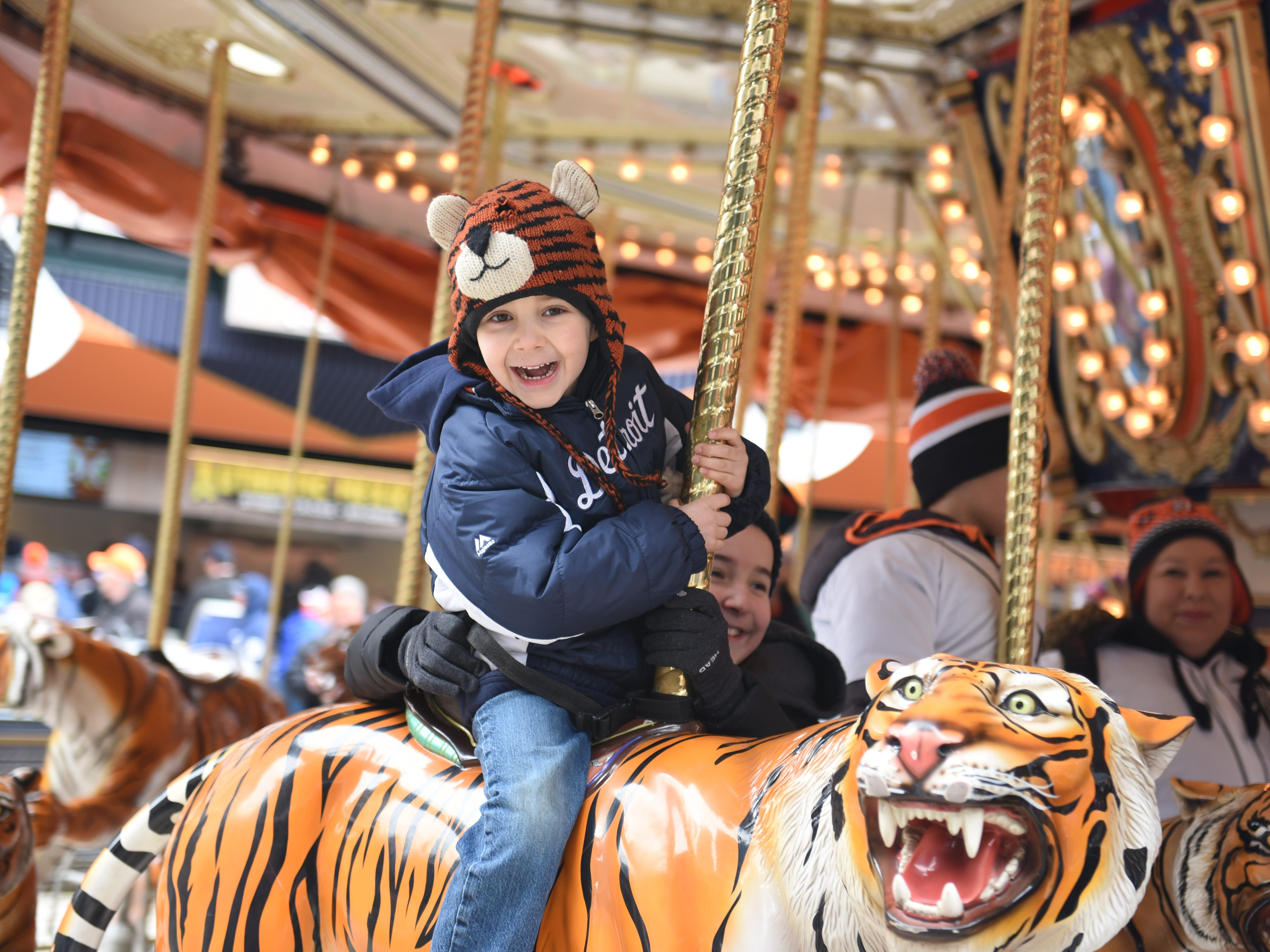 Luke Merdinian of Brighton smiles as he his held by his sister Kate on Opening Day at Comerica Park on March 30, 2018.