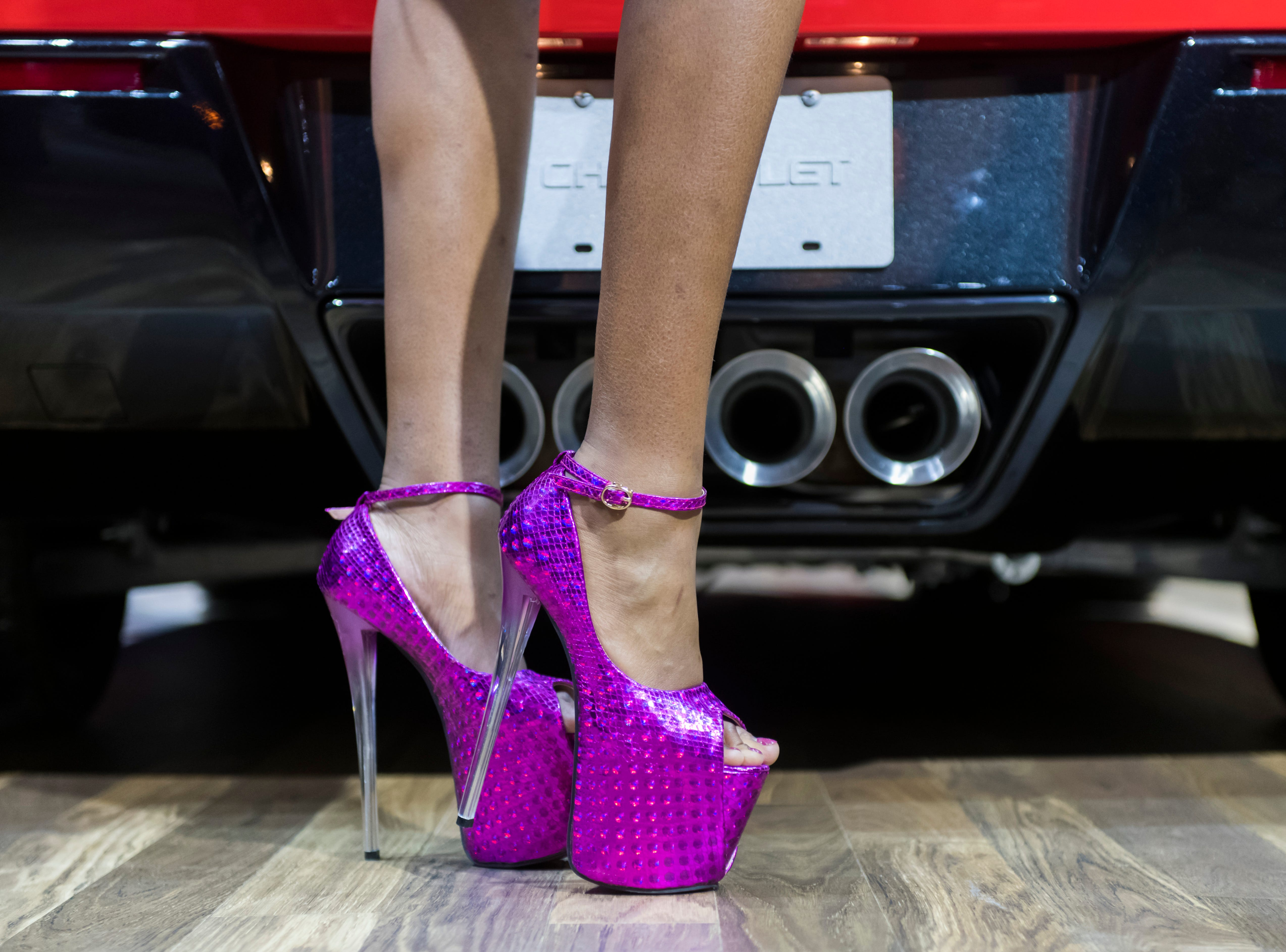 Jae'lyn Ware, of Warren, shows off her high heels behind a Chevrolet Corvette during the charity preview of the North American International Auto Show at Cobo Center in Detroit, January 19, 2018.