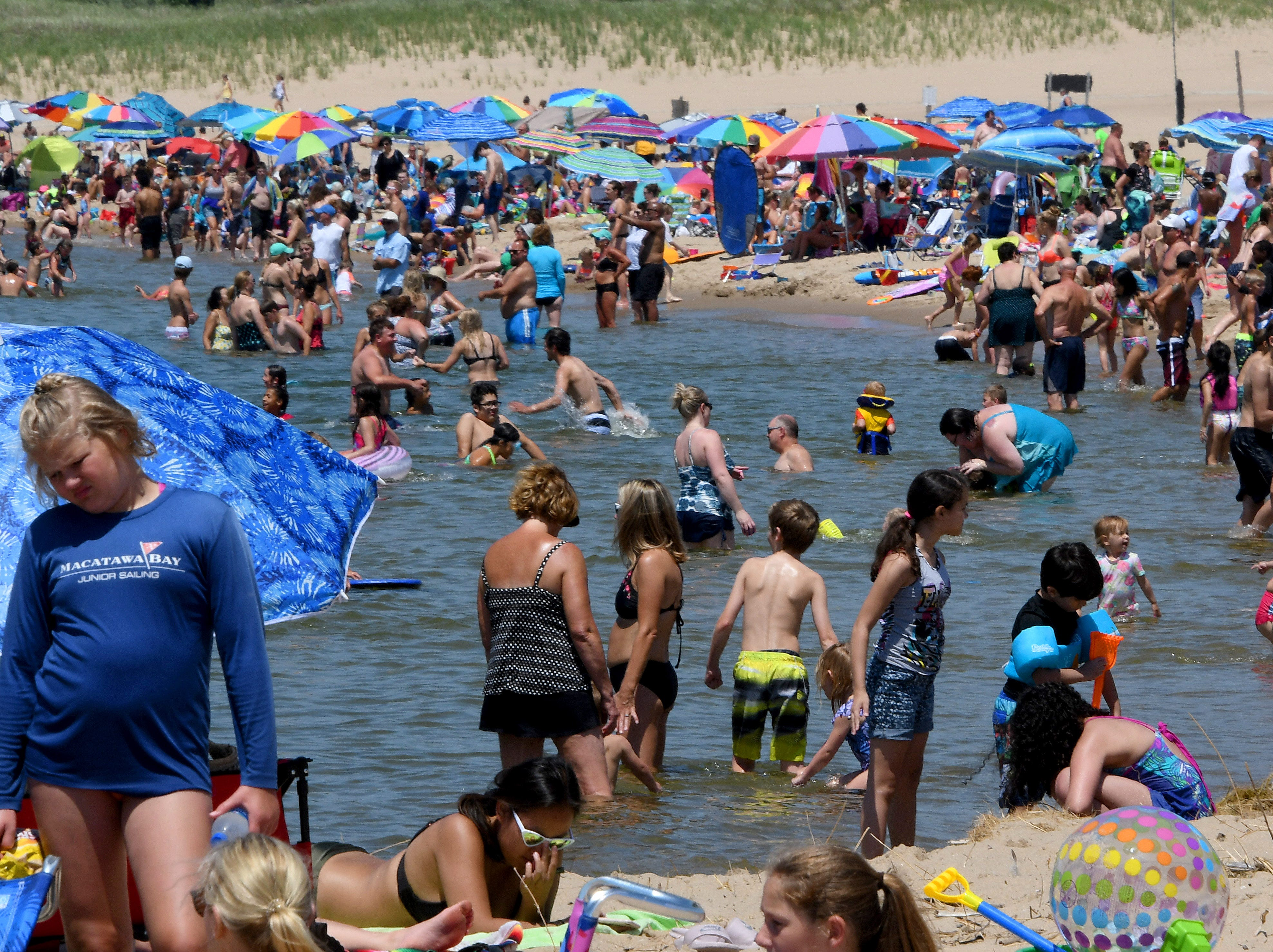 Crowds flock to Ottawa Beach, part of Holland State Park, on Lake Michigan on Friday, June 29, 2018.  Also shots of boats in the channel with the Holland Light in the background.   (Dale G.Young/Detroit News) 2018.