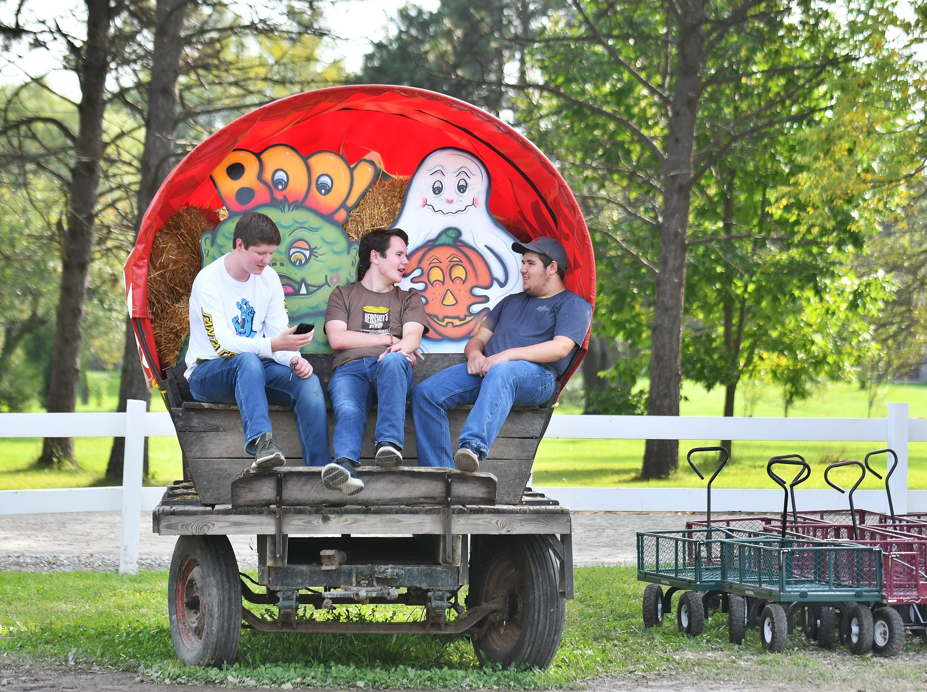 From left, Adam Bright, 16, Connor Moore, 16, and Griffin Lumetta, 16, all of Canton, decided to meet up at Plymouth Orchards and Cider Mill after they got out of school on October 3, 2018.
