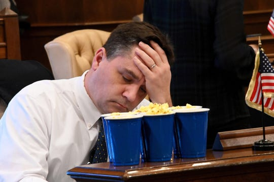 Sen. Pat Colbeck, R-Canton, is stocked up with popcorn, but holds his head in his hands, facing a long night Thursday in the  Michigan senate.