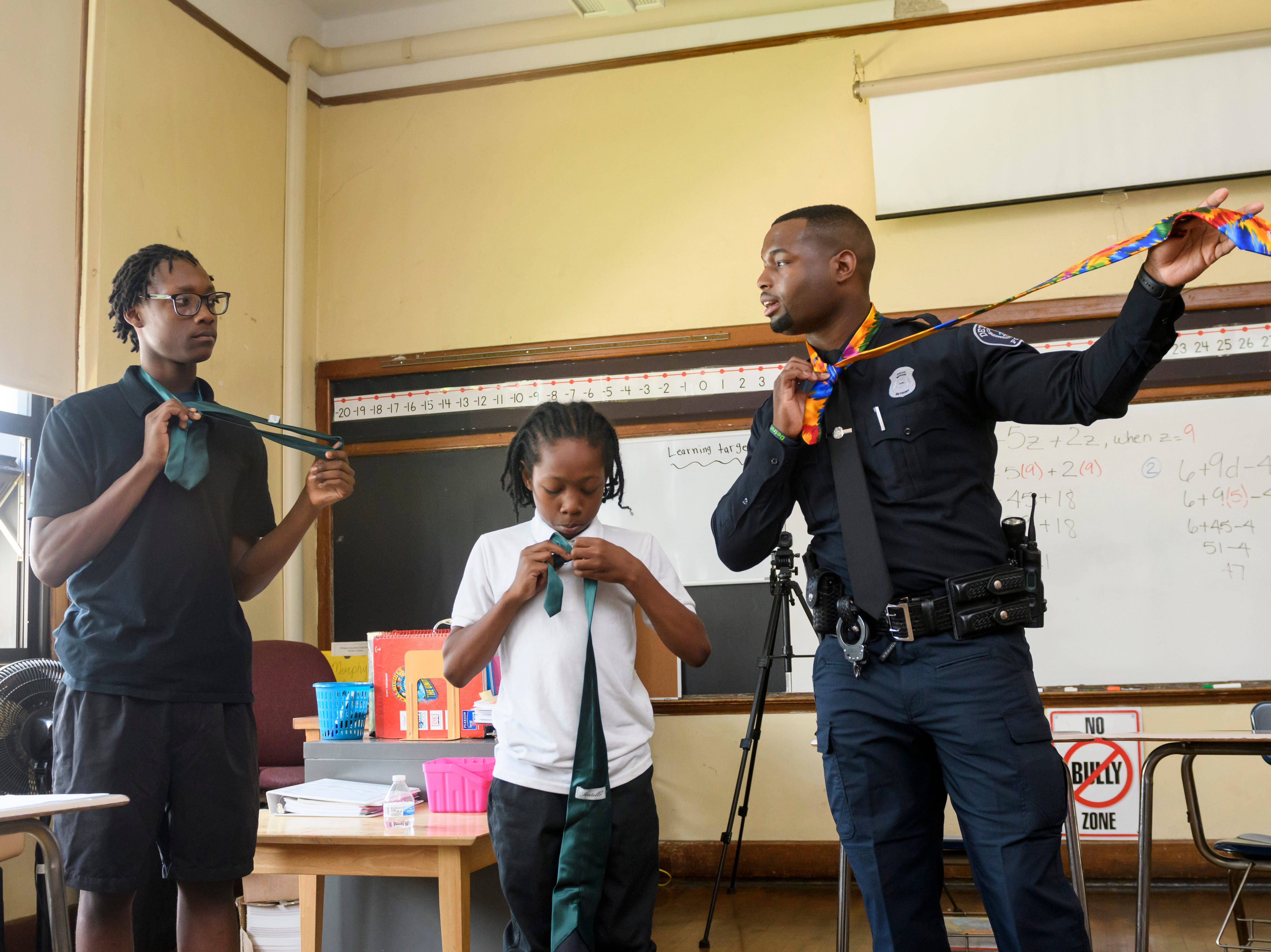 Students Donovan Reed, left, and Damani Qualls are taught how to tie a necktie by Detroit police officer Bryant George,  as part of a PAL program at Murphy Academy in Detroit, June 4, 2018.  George was named of the 2018 class of Detroit News Michiganians of the Year.