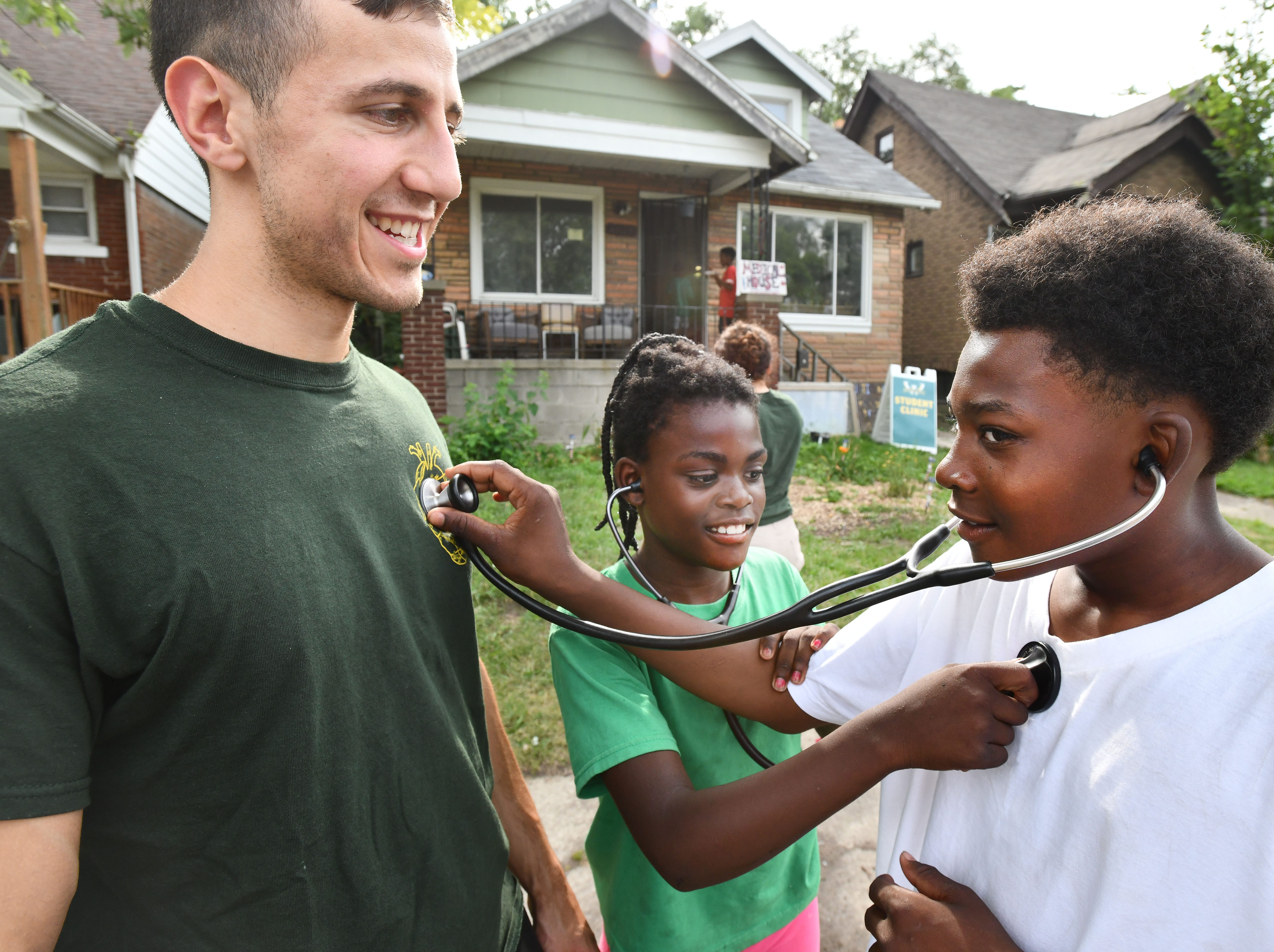 WSU medical student Ali Dakka lets Justin Brown use his stethoscope, listening for a heartbeat, as Jiya Brown, 10, listens for Justin's heartbeat, on August 8, 2018. Wayne State medical students set up a clinic as part of the community center known as Auntie Na's House, providing much-needed medical services for the Detroit neighborhood.