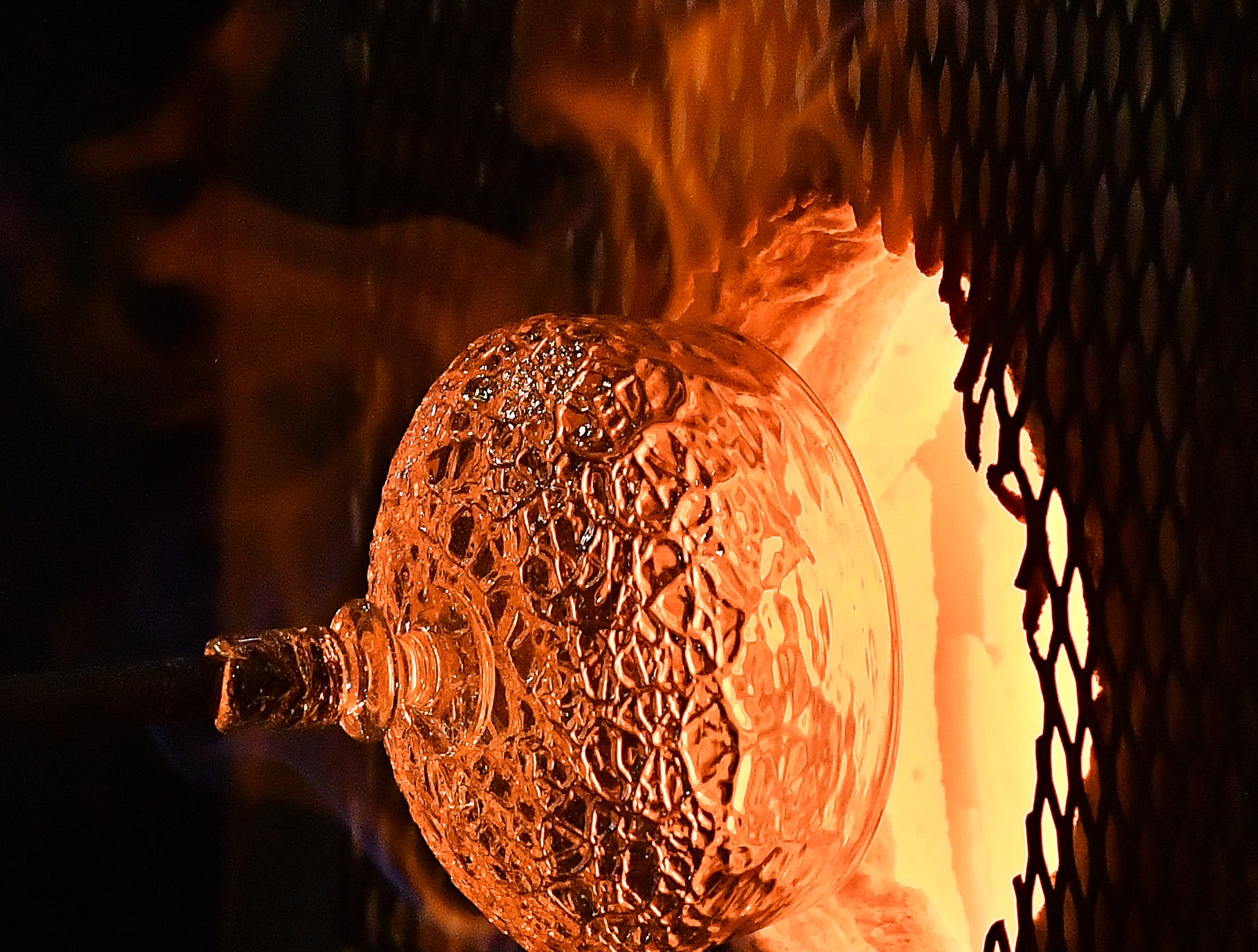 The top of a glass goblet comes out of the fire, created by artists Louie Sanchez and Rebecca Silverman, at the Russell Industrial Center in Detroit on July 20, 2018. The nonprofit Michigan Glass Project holds annual events to raise funds for local causes.