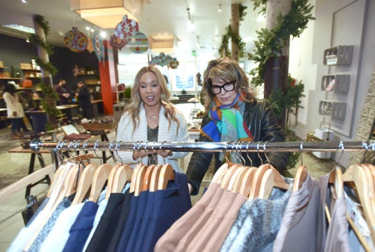 Avabelle Boutique owner/buyer Randee Garrett, left, of Westland, helps customer Connie Cessante, of Plymouth, as she looks through Avabelle's clothing at 1441 Woodward Collective. Garrett is one of 13 local business owners at the pop-up space that operates from May through December 27th.