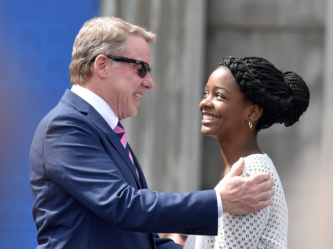 Ford Executive Chairman Bill Ford Jr. hugs Asia Newson, Detroit's Youngest Entrepreneur, after she introduces the chairman at the old Michigan Central Station in Detroit, June 19, 2018, for a party celebrating Ford's purchase of the building.