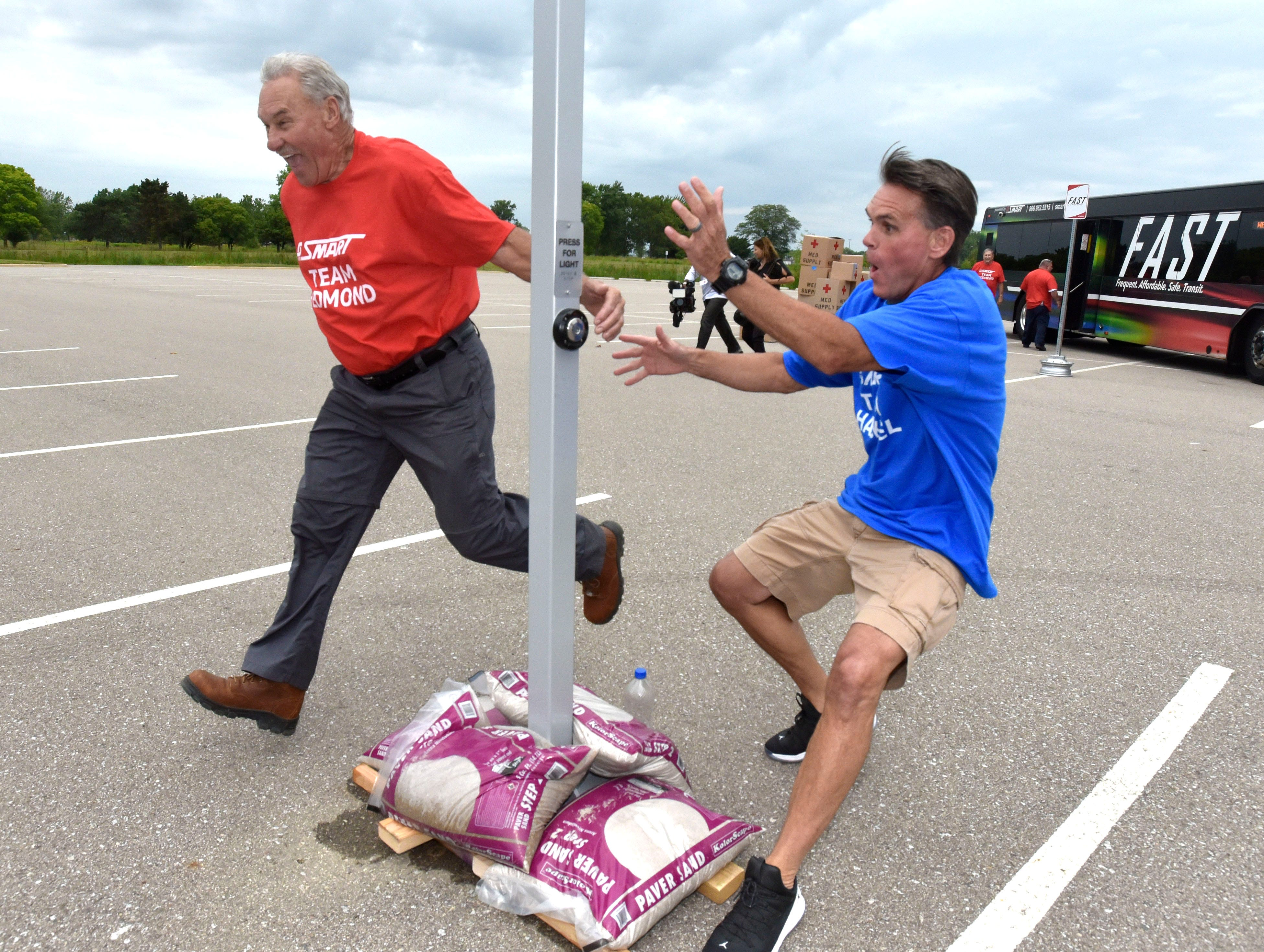 Red Wings great Mickey Redmond, left, laughs as he pushes the finish button just before Macomb County Executive Mark Hackel during a race at Lake St. Clair Metropark in Harrison Twp., August 1, 2018. The SMART regional transit system was demonstrating the importance of buses during a potential disaster, with two teams loading emergency supplies on and off the vehicles to see which had the fastest response time.
