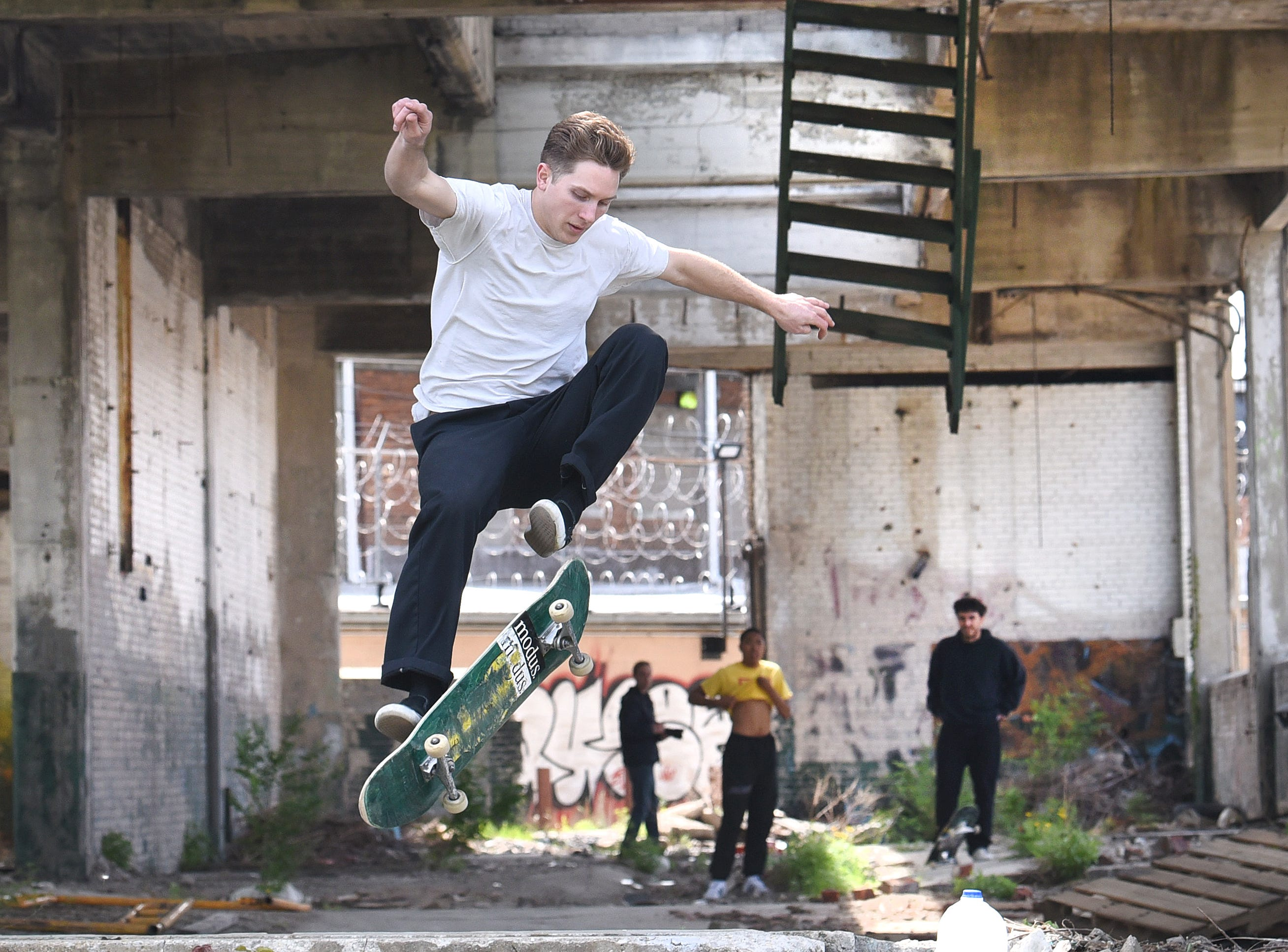 Skater Jeff Srnec, of Winnipeg, Canada, catches some air off a loading dock ramp as fellow Canadian skaters watch inside an abandoned building near Eastern Market in Detroit on May 18, 2018.