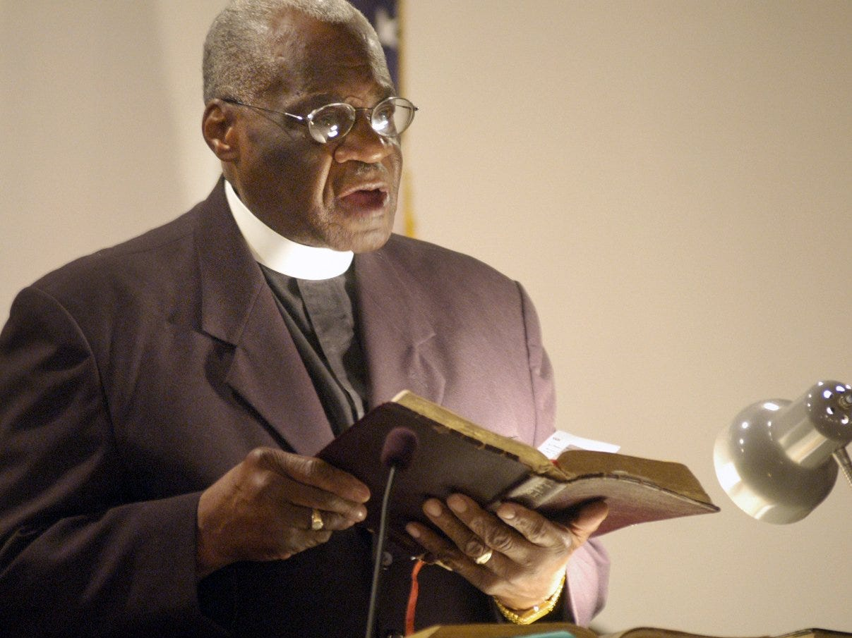 The Rev. Cephus McGee, of All Saints Home Church of God in Christ in Elmira, reads from the Bible in 2005.