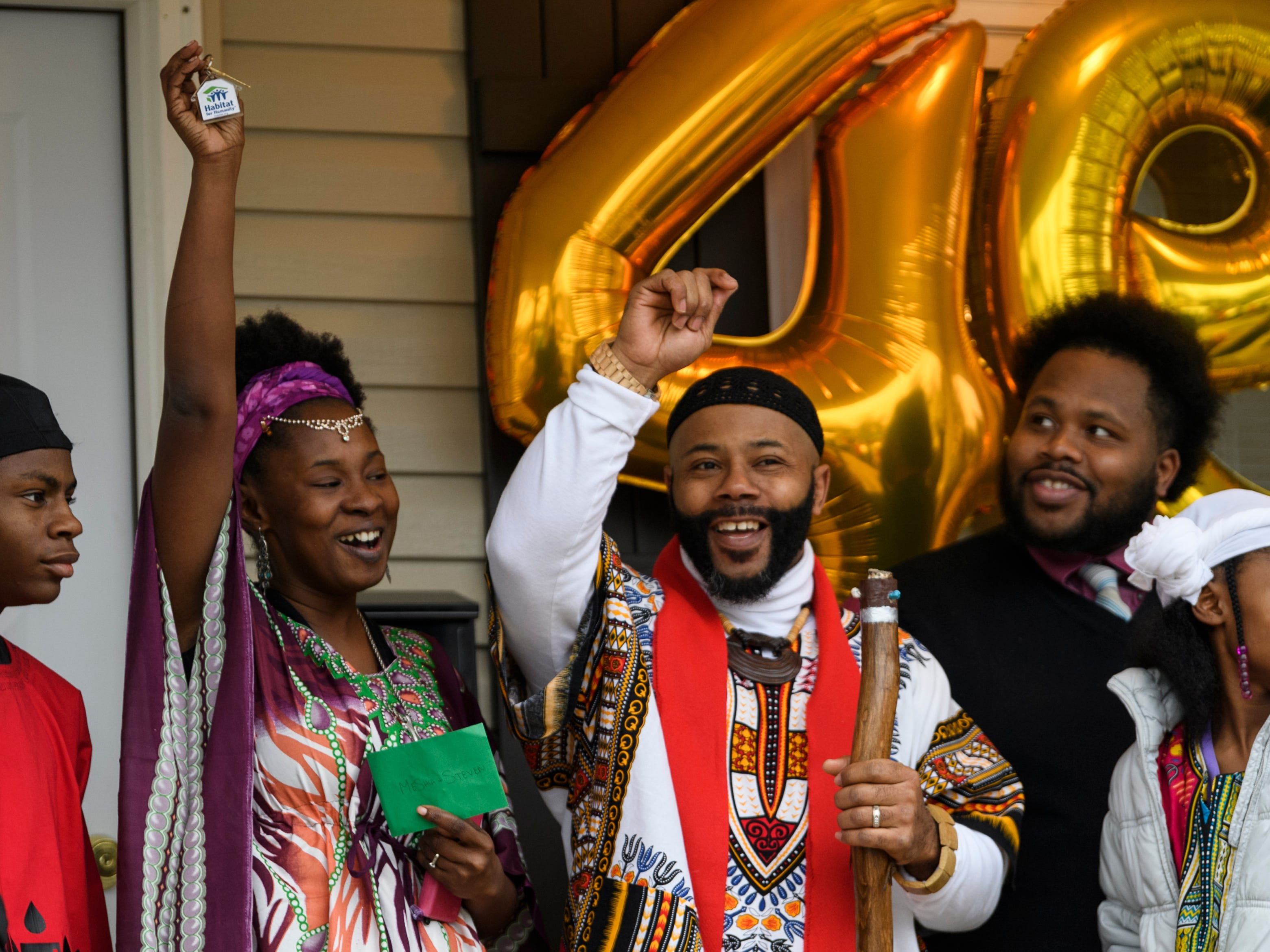 MeShia, center left, and Steven Kince, center right, react to being handed the keys to their new home as they stand on the porch with their family during the 500th Habitat for Humanity home dedication ceremony on Bedford Avenue in Evansville, Ind., Thursday afternoon, Dec. 20, 2018. Four new homeowners were recognized during the event with ceremonial ribbon cuttings and gift-giving in front of each home.