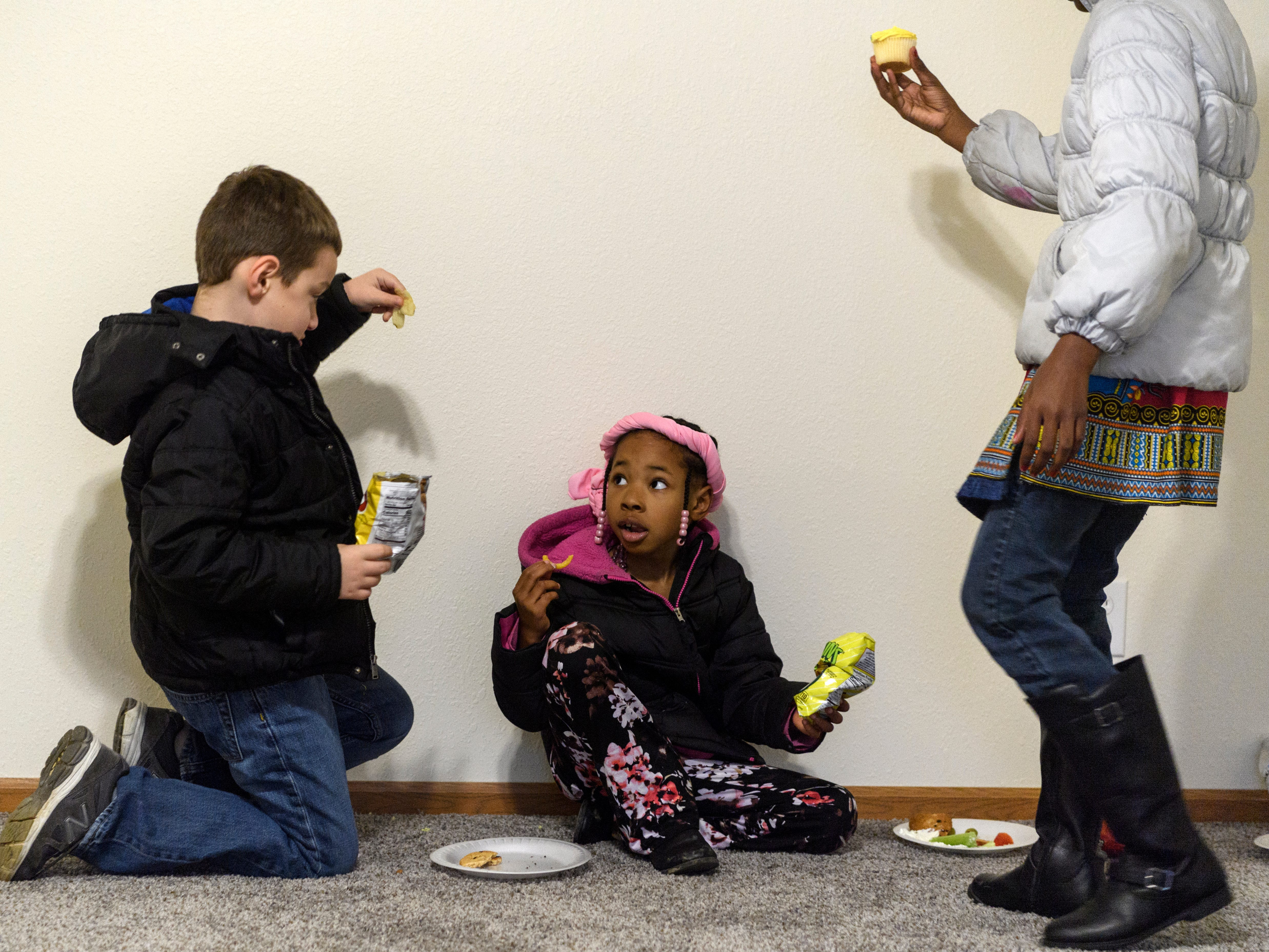 Shane Barclay, 7, from left, chats with Zorea Kince, 7, and A'miah Kince, 9, as they eat snacks in the living room of the new Kince family home following the 500th Habitat for Humanity home dedication ceremony on Bedford Avenue in Evansville, Ind., Thursday, Dec. 20, 2018. The Kinces built a five bedroom home that features two bathrooms and ample kitchen and living room space.