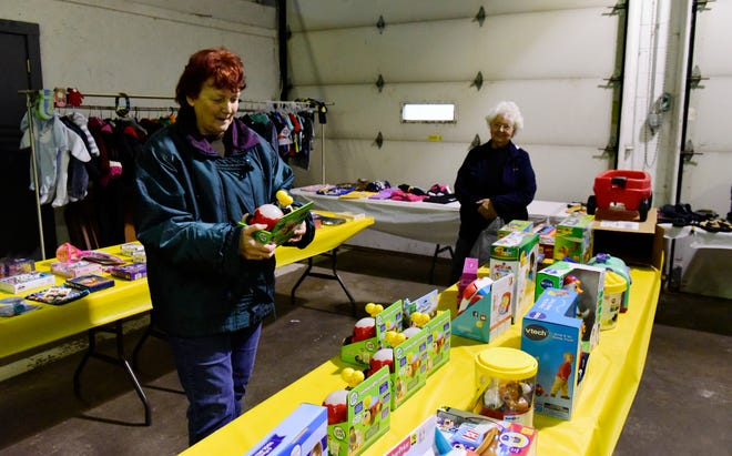 Karen Zerman of Clyde, left, picks out toys for her six month old great grandson while volunteer Sue Rohrbach of Green Springs helps at Caring For Clyde Kids community toy collection in Clyde on Thursday afternoon.