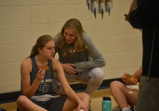 Sami Steffeck, right, talks to sister Ashley Steffeck during a break from the Fossil Ridge girls basketball team's annual kickball game Wednesday at the SaberCats gym.