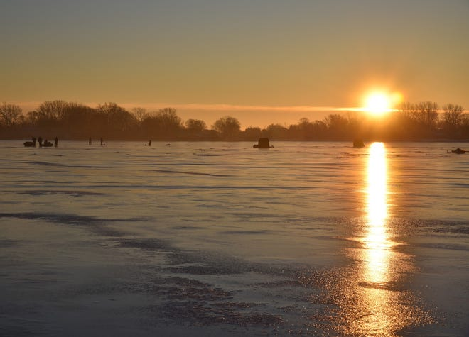 The sun rises Dec. 15 as ice fishermen go after perch and bluegills on Lake Winnebago.