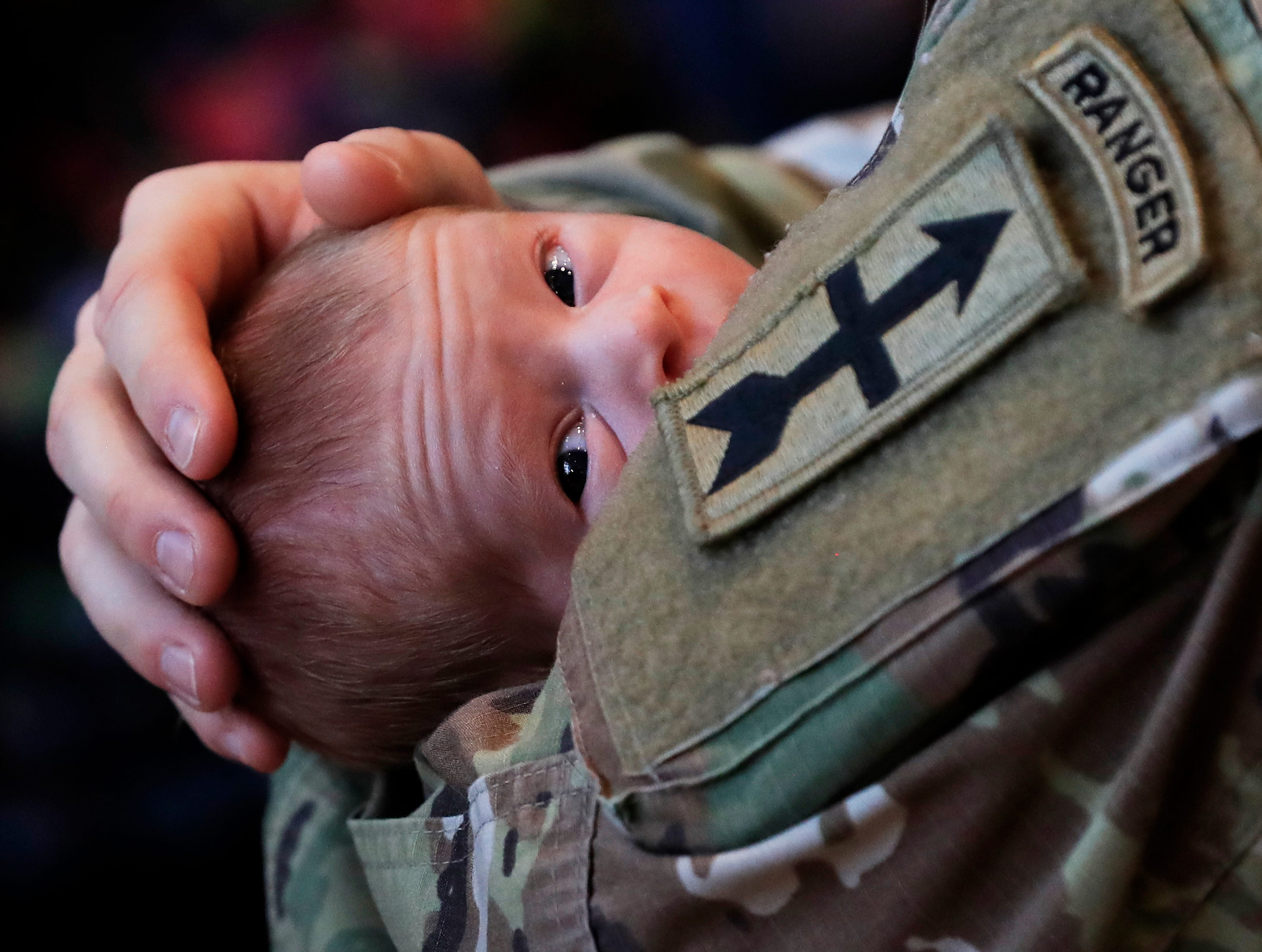 Platoon Leader Anthony Pinchuk of Green Bay holds his son William after a sendoff ceremony for the Wisconsin Army National Guard 2nd Battalion, 127th Infantry at the Lambeau Field Atrium on Thursday, November 29, 2018 in Green Bay, Wis.
