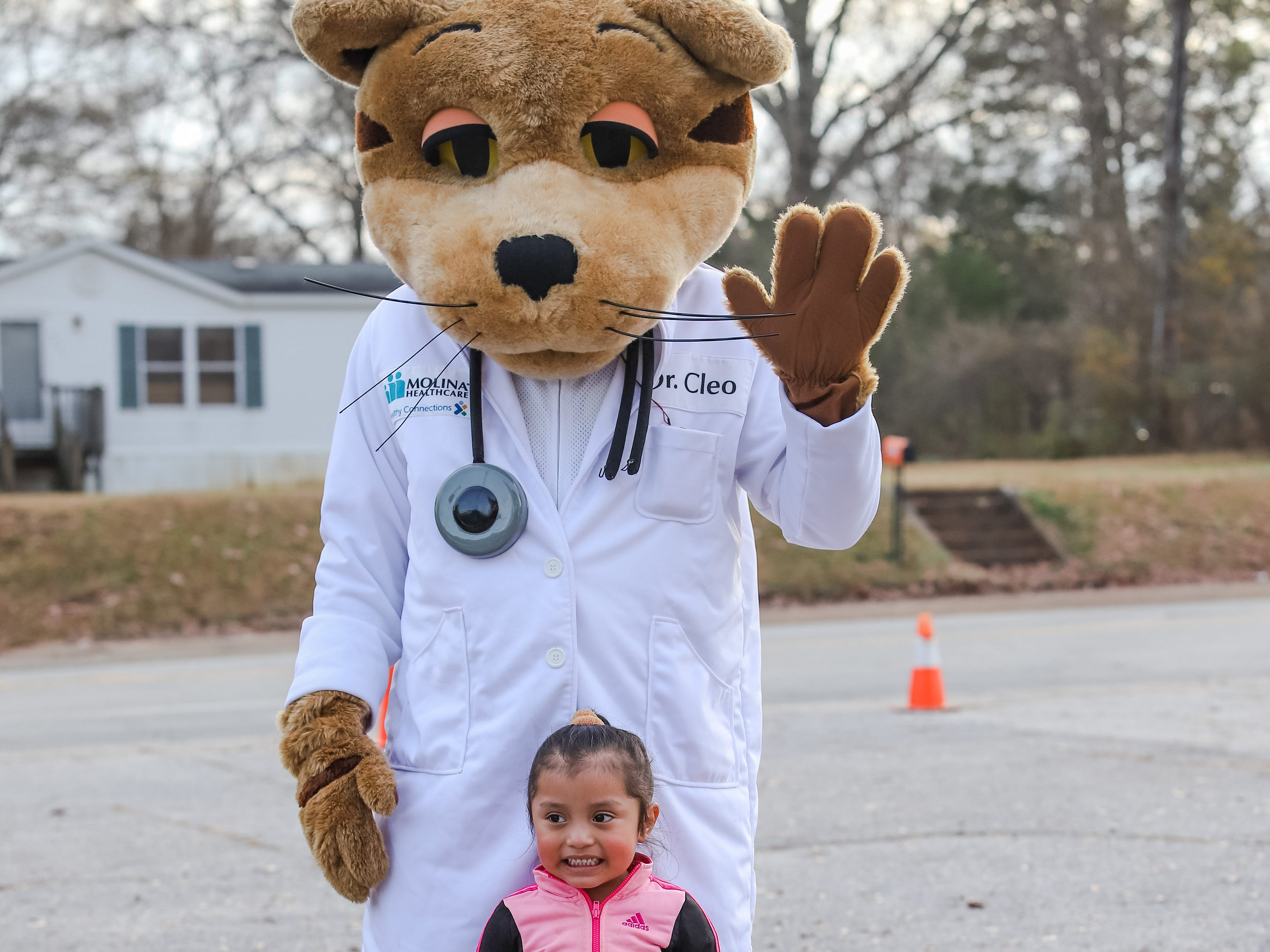 "Three year old Gesela Pascual-Marcos poses with the Molina bear.  Molina Healthcare of  South Carolina and Duncan Chapel  Elementary  School  hosted  ""Christmas in the Community; to  get into the season of giving and spread holiday cheer among Greenville residents on Wednesday, Dec. 19, 2018."