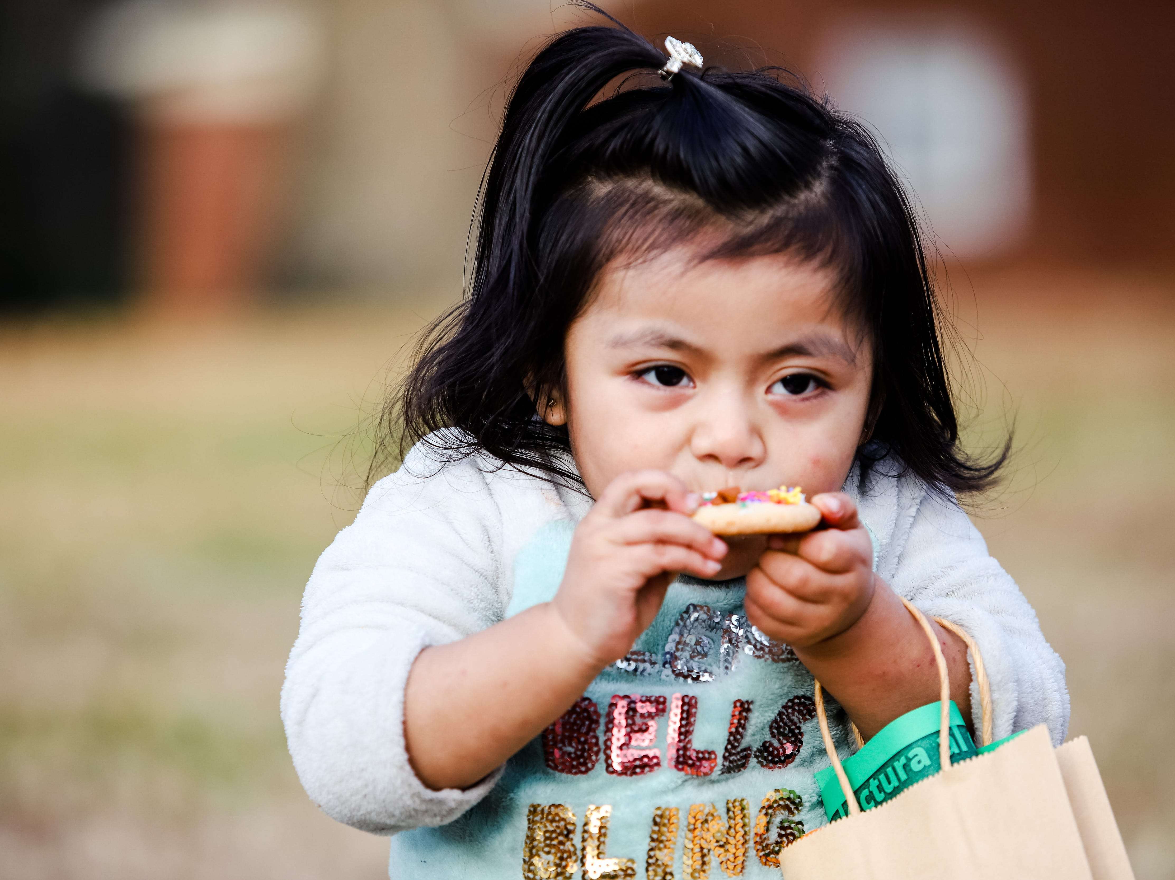 "Three year old Bee Jaun enjoys a decorated sugar cookie.  Molina Healthcare of  South Carolina and Duncan Chapel  Elementary  School  hosted  ""Christmas in the Community; to  get into the season of giving and spread holiday cheer among Greenville residents on Wednesday, Dec. 19, 2018."