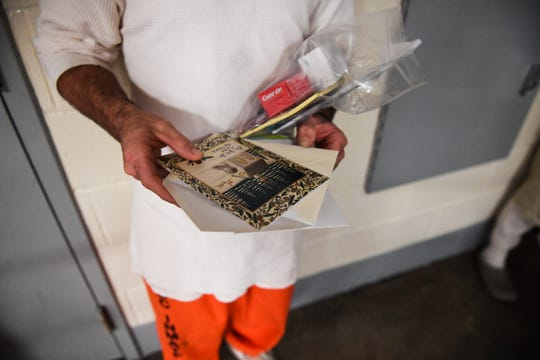 An inmate at Perry Correctional Institution holds the contents of a Christmas gift package on Tuesday, Dec. 4, 2018.