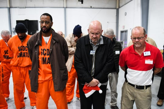 Inmates and volunteers pray together at Perry Correctional Institution after a Christmas gift giving event on Tuesday, Dec. 4, 2018.