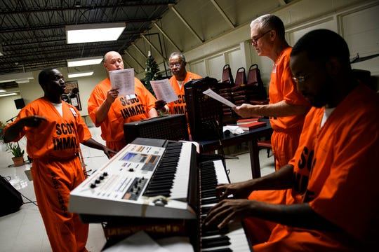 Inmates at Perry Correctional Institution sing Christmas carols during a special holiday dinner on Monday, Dec. 10, 2018.