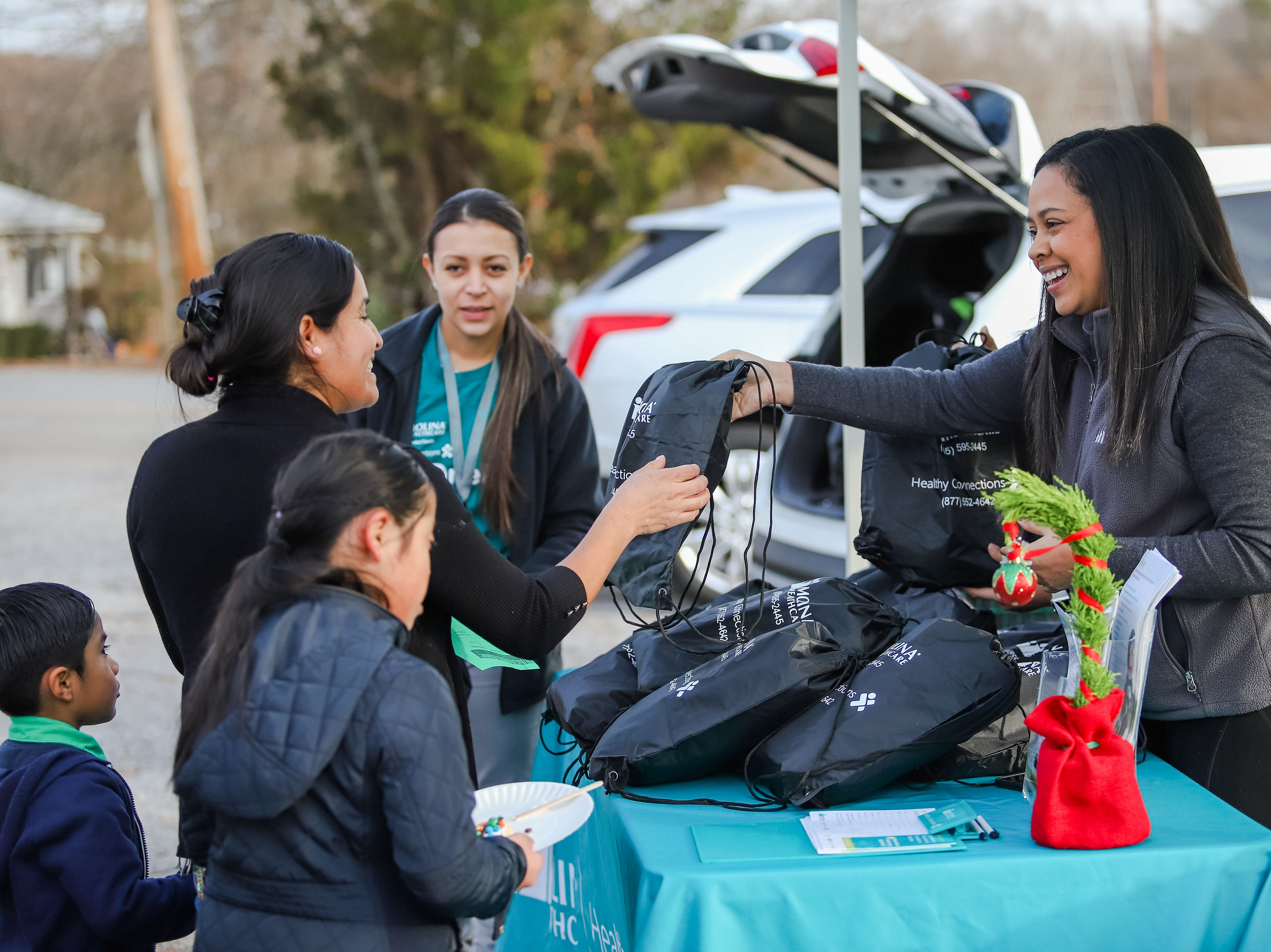 "Johanna Perez passes out blankets to the Clemente family.  Molina Healthcare of  South Carolina and Duncan Chapel  Elementary  School  hosted  ""Christmas in the Community; to  get into the season of giving and spread holiday cheer among Greenville residents on Wednesday, Dec. 19, 2018."