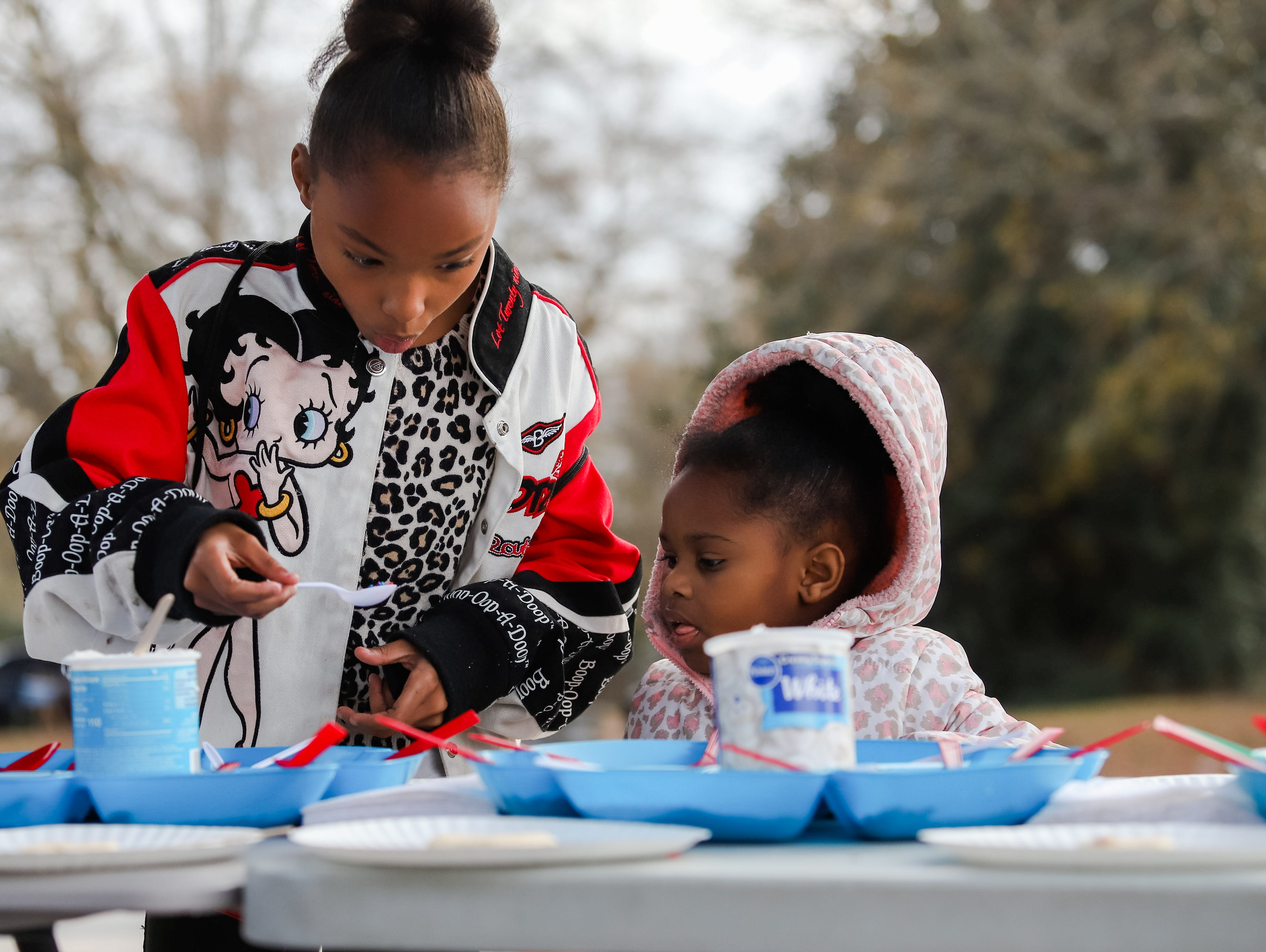 "Sisters Amari Spencer (8) and Amina Harris (3) work on decorating some Christmas cookies. Molina Healthcare of  South Carolina and Duncan Chapel  Elementary  School  hosted  ""Christmas in the Community; to  get into the season of giving and spread holiday cheer among Greenville residents on Wednesday, Dec. 19, 2018."