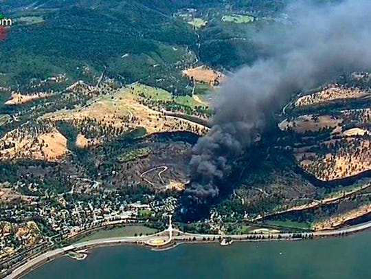 In this June 3, 2016, file image, from video provided by KGW-TV, smoke billows from a Union Pacific train that derailed near Mosier, Ore., in the scenic Columbia River Gorge.