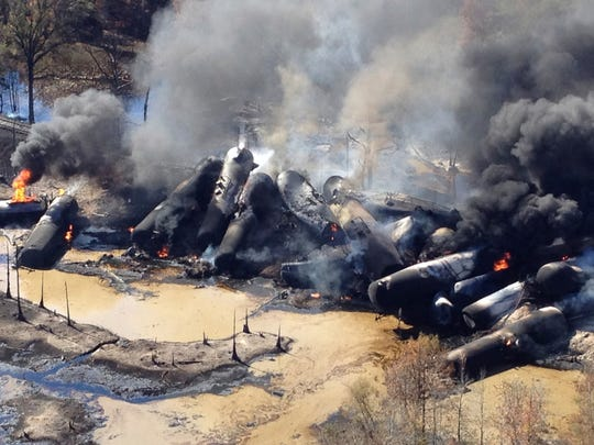 In this Nov. 8, 2013 file photo, a tanker train carrying crude oil burns after derailing in western Alabama outside Aliceville, Ala.
