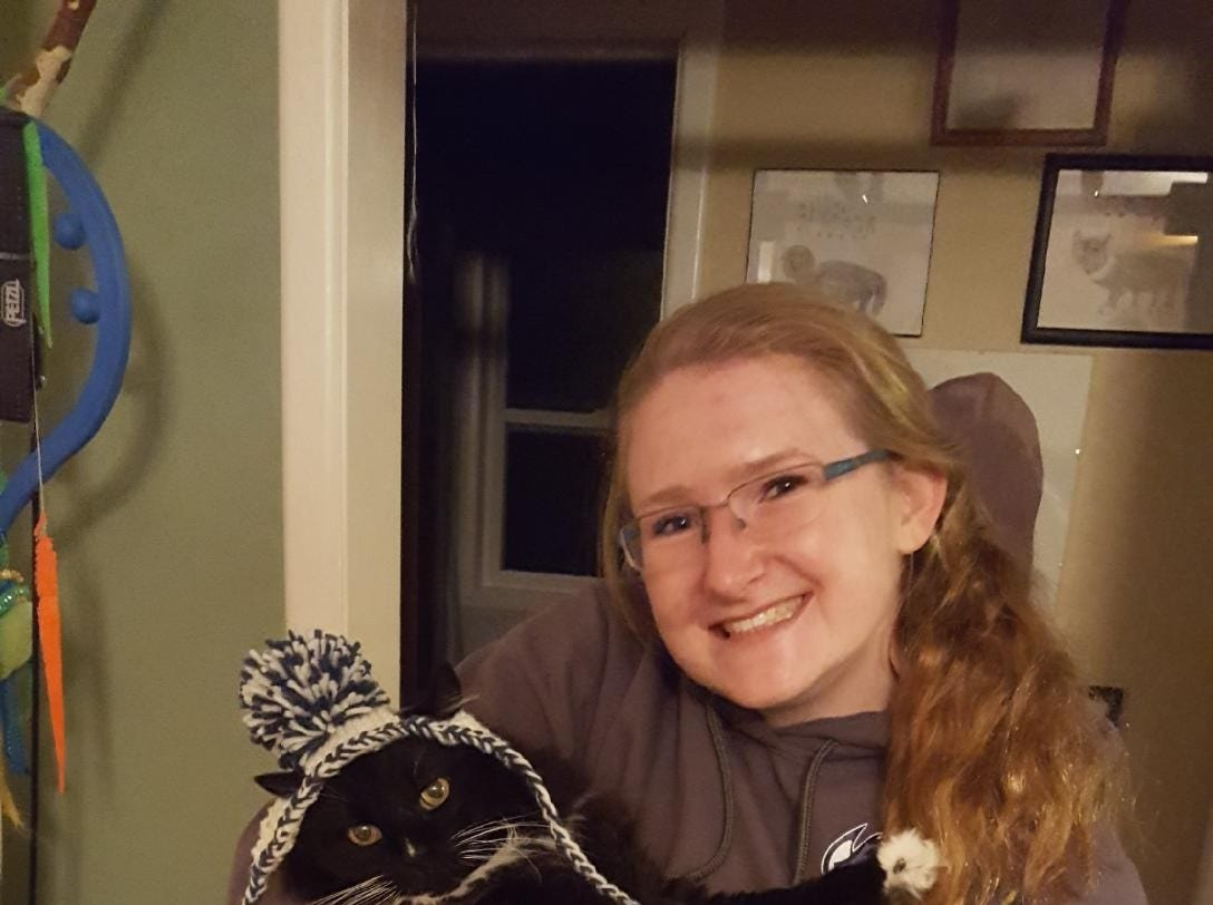 """Jennie Gresham knits """"Cat Hats"""" for friends, family and by request, asking only that recipients donate to the Maclean Animal Adoption Center in return.  Owners take photos and send their cats' """"comment"""" on the hat. Gresham is shown here with her cat, Daffodil Cheesecake."""