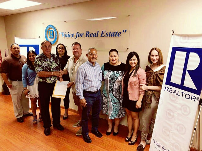 The Guam Association of Realtors presents a check for $10,000 to the Ayuda Foundation for post-Yutu relief efforts in the CNMI.