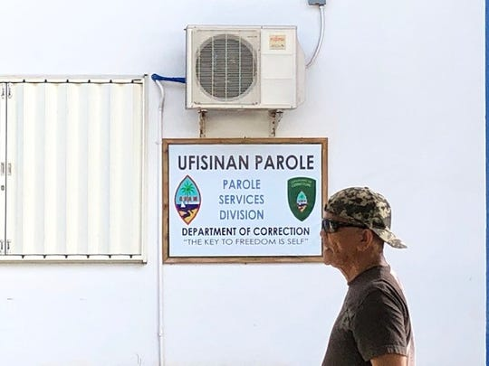 A man walks past a sign for the office of the Parole Services Division, which is an office space in the Paseo De Susana that's being shared by the Guam Pardon Review Board.