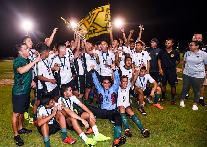The John F. Kennedy Islanders boys' soccer team and others celebrates after defeating the Harvest Christian Academy Eagles, 3-1, to capture the IIAAG High School Boys Soccer championship at the Guam Football Association National Training Center on Wednesday, Dec 19, 2018.