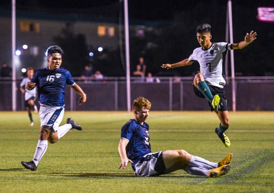 The John F. Kennedy Islanders Edward Cho (7) takes to the air to avoid a collison with Harvest Christian Academy Eagles' Ethan Elwell (15) during the IIAAG High School Boys Soccer championship at the Guam Football Association National Training Center on Wednesday, Dec 19, 2018. The Eagles score the first and only goal during the first half but the Islanders came back strong to score three goals in the second half, to capture the league championship with a final score of 3-1.