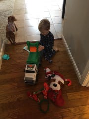 Two-year-old Remington Tennyson play with the gifts that a city sanitation crew brought him after he and his mother gave them hot chocolate one morning. His mom said he waits to see the crew in action every Wednesday morning.