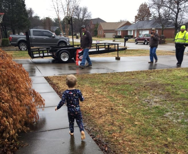 Remington Tennyson runs to see a city sanitation crew that brought him some Christmas presents.