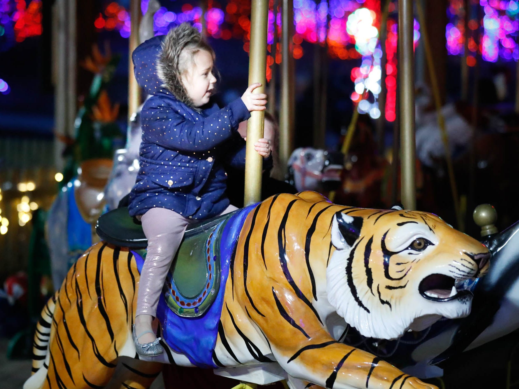 Zoey Miller, left, and Molly Collelo, right, ride the carosel  during Christmas at the Indianapolis Zoo on Wednesday, Dec. 19, 2018.