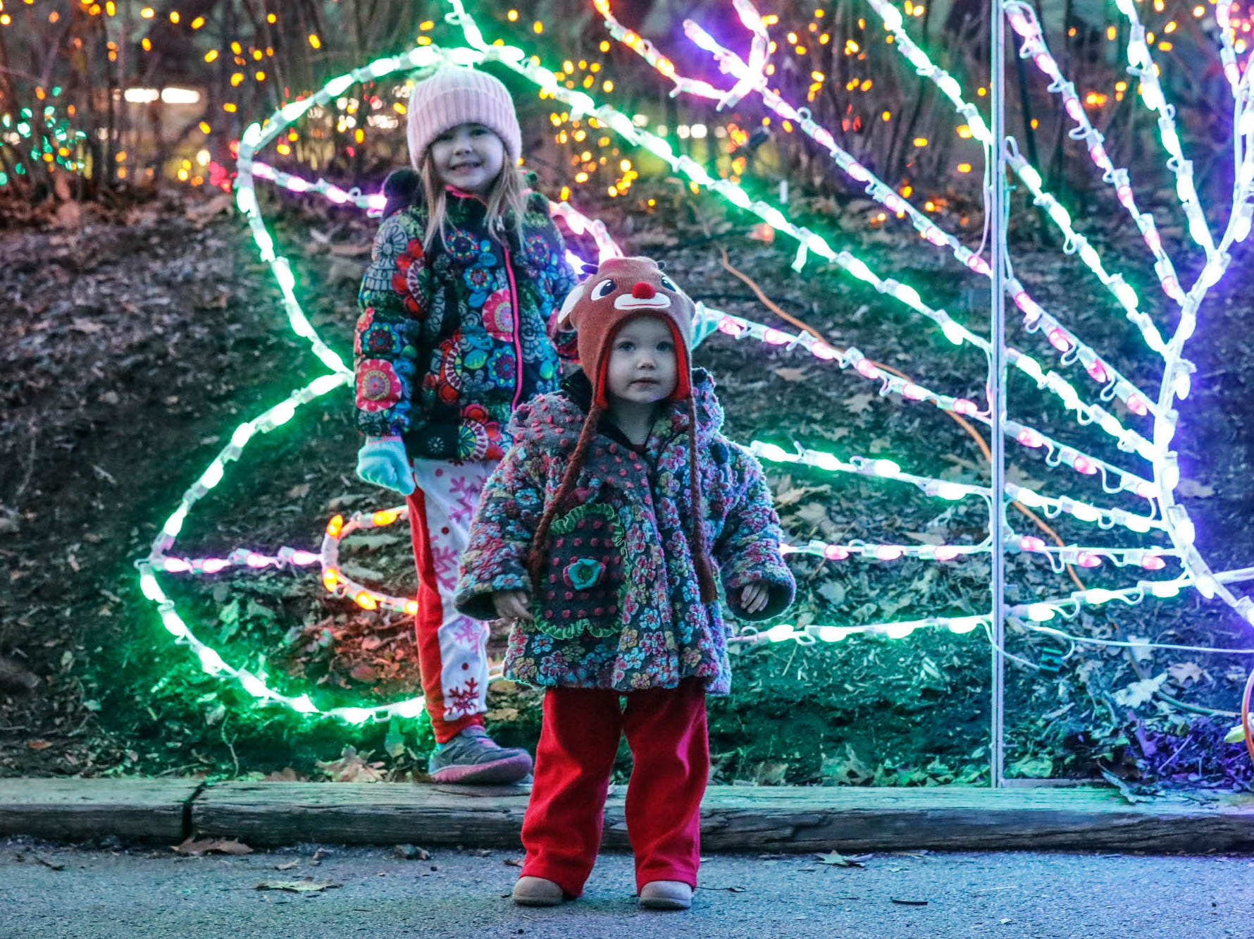 Avaline, left, and Annmarie Dewsbury pose for photos by a lighted peacock during Christmas at the Indianapolis Zoo on Wednesday, Dec. 19, 2018.