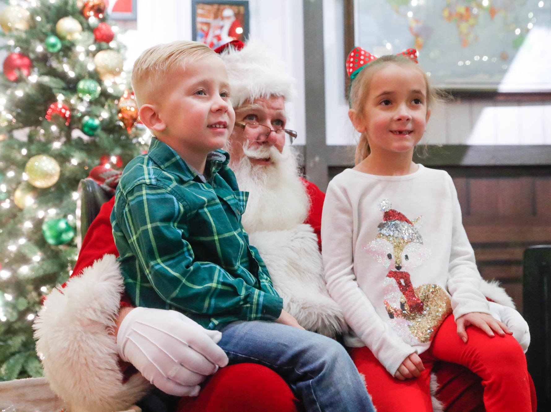Steven and Genevieve Crawley sit on Santa's lap during Christmas at the Indianapolis Zoo on Wednesday, Dec. 19, 2018.