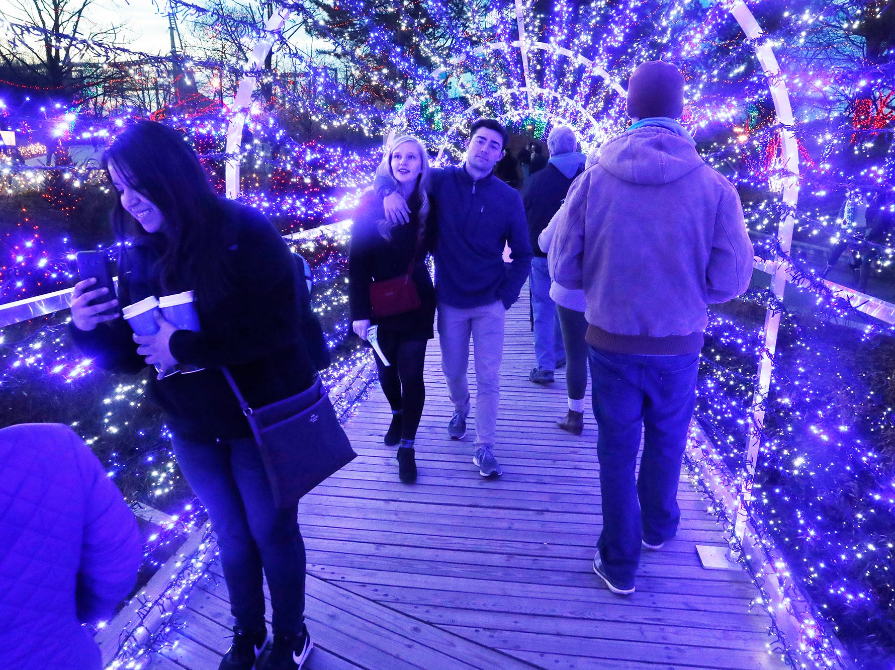 Guests stroll through a lighted tunnel during Christmas at the Indianapolis Zoo on Wednesday, Dec. 19, 2018.
