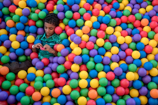 Sanjiv Balaji, 5, lays back in a ball pit inside the Big Bounce America inflatable attraction at Waterman's Family Farm in Indianapolis, Friday, Sept. 14, 2018. The world's largest bounce house covers 10,000 square feet and will be in Indy though September 16.