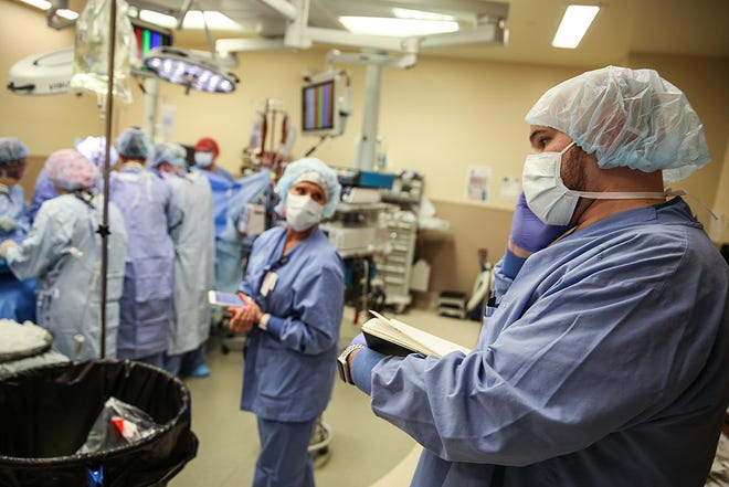 At right, Steven Ashley and other organ recovery coordinators communicate constantly during procurement surgery, with transplant centers, research centers, recipient hospitals and others involved in the complex process.