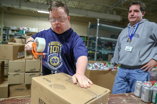 Chris Foy (left) packs 18 cans of pop into a box, with help from Tony Baugh, a direct support professional with Noble of Indiana, at St. Vincent de Paul Food Pantry on Thursday, Dec. 20, 2018. Foy has volunteered at the pantry for 10 years, six of which with Baugh. Foy spends two hours every Thursday packing or sorting various foods and also volunteers on Wednesdays with his father, Dave, driving food to those without transportation. Noble aims to give opportunities and enhance the quality of life for people with disabilities through individualized services.
