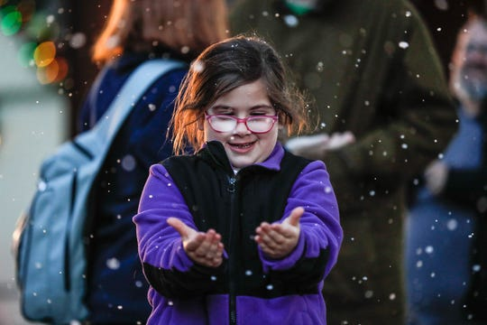 Meredith Gomes frolics in fake snow during Christmas at the Indianapolis Zoo on Wednesday, Dec. 19, 2018.