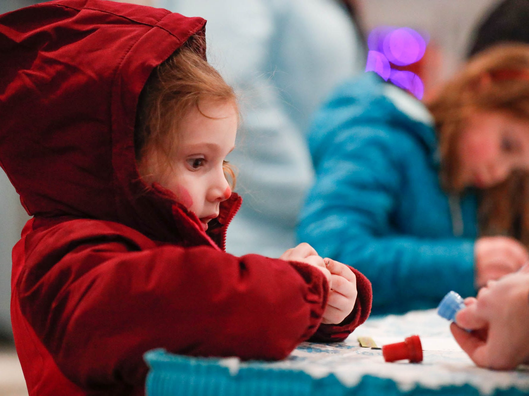 Ellie Shanahan creates a Christmas postcard during Christmas at the Indianapolis Zoo on Wednesday, Dec. 19, 2018.