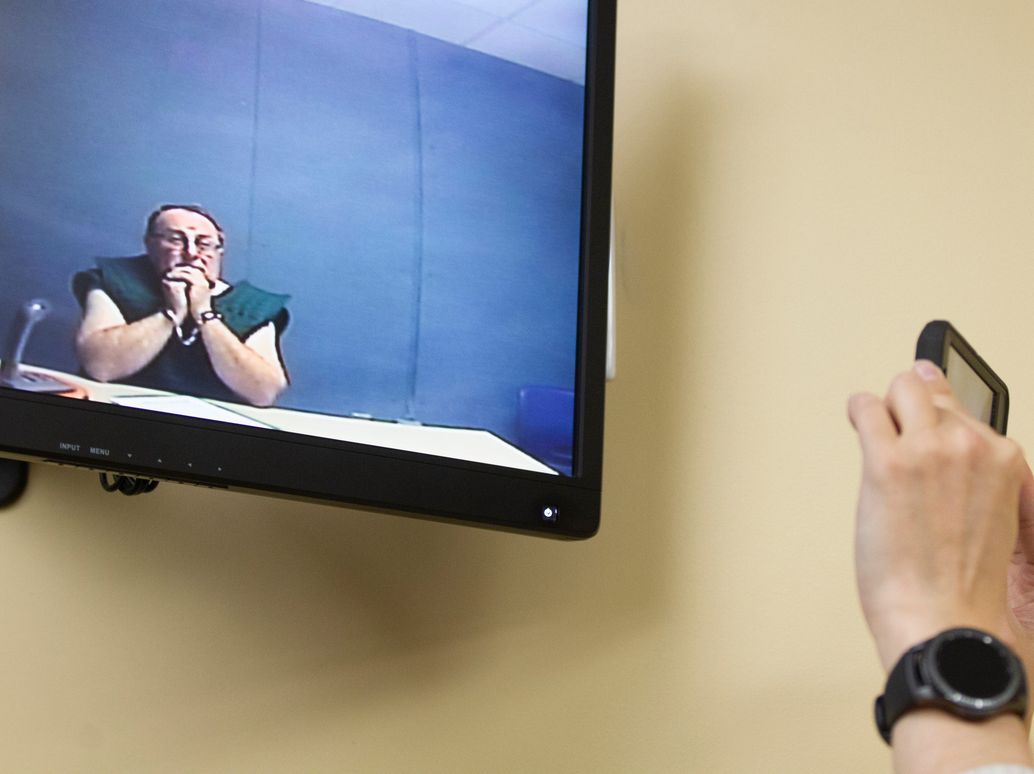 A TV reporter takes video of Jerry Lynn Burns during his initial appearance on a video monitor from the Linn County Jail on Thursday, Dec. 20, 2018, at the Linn County Courthouse in Cedar Rapids.