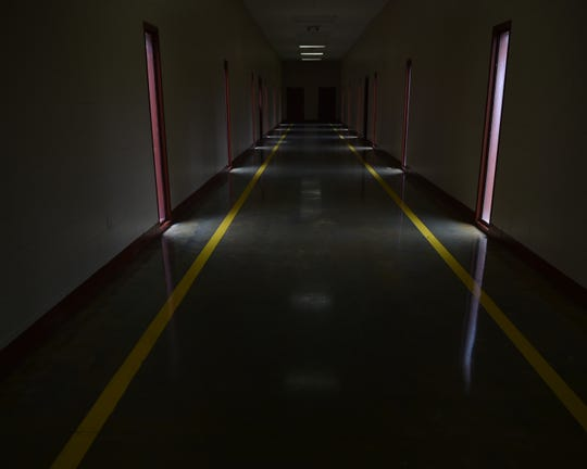 A hallway connecting cell blocks sits in darkness at the currently closed Walnut Grove Correctional Facility. Built in 2001 the correctional facility housed approximately 1500 inmates by the time the controversial institution was shut down in 2016. Thursday, Dec. 20, 2018