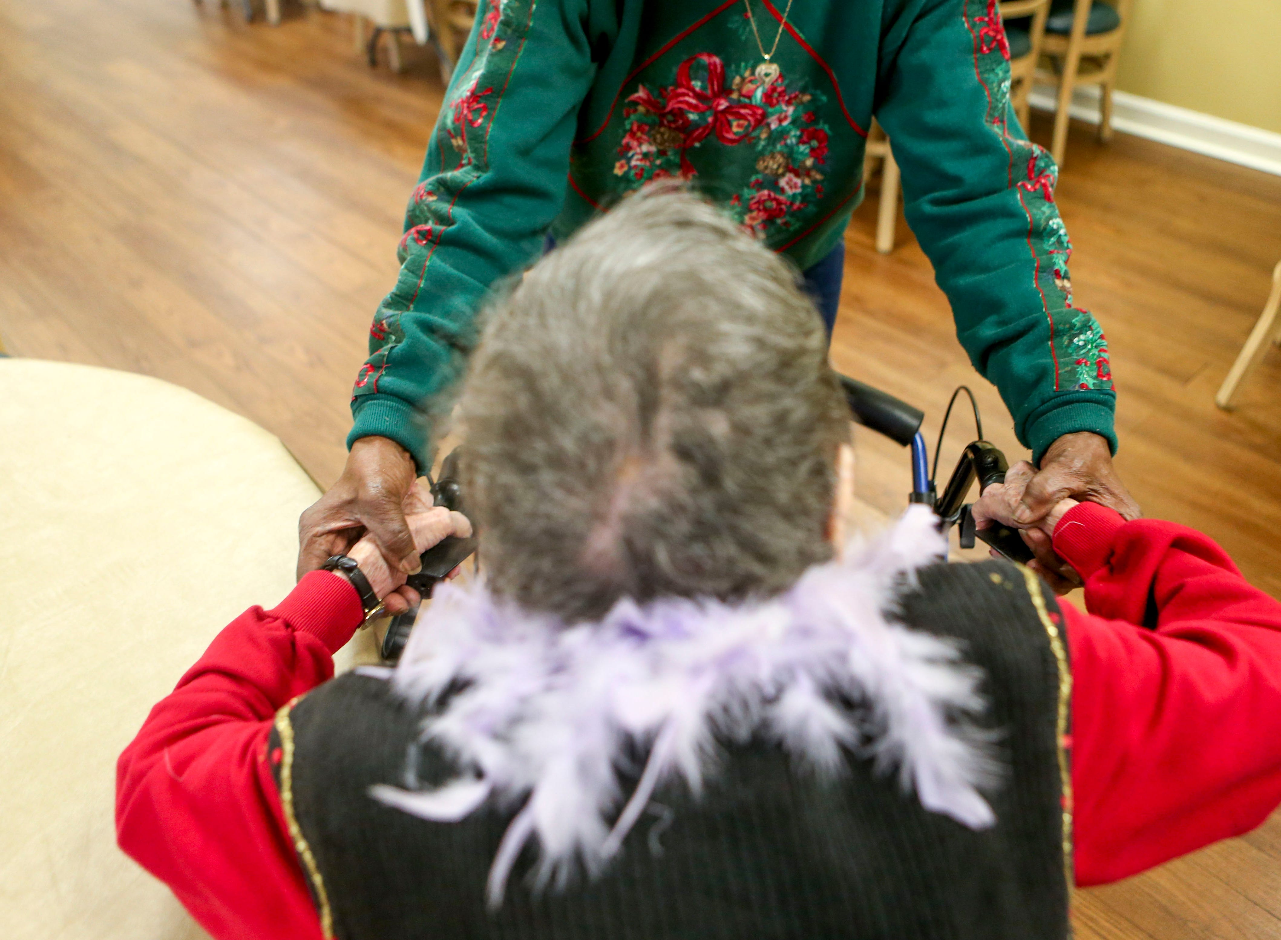 Anne Boston assists Ida Feldman get up from her chair and onto her walker at Regency Retirement Home in Jackson, Tenn., on Thursday, Dec. 20, 2018.