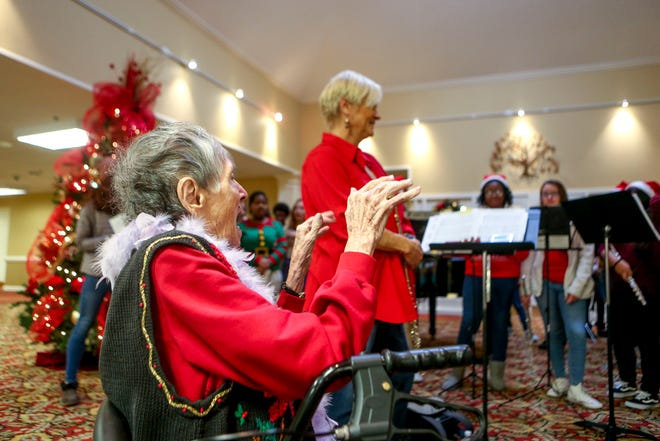 Ida Feldman raises her hands mimicking a conductor while members of the Madison Academic High School choir and band perform for residents at Regency Retirement Home in Jackson, Tenn., on Thursday, Dec. 20, 2018.