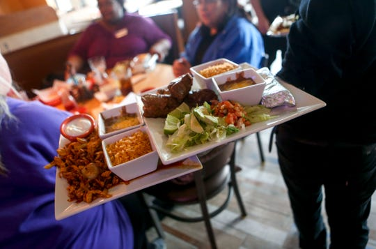 A server delivers multiple dishes in one trip to a table during the opening day at Te'Kila Mexican Bar & Grill in Jackson, Tenn., on Wednesday, Dec. 19, 2018.