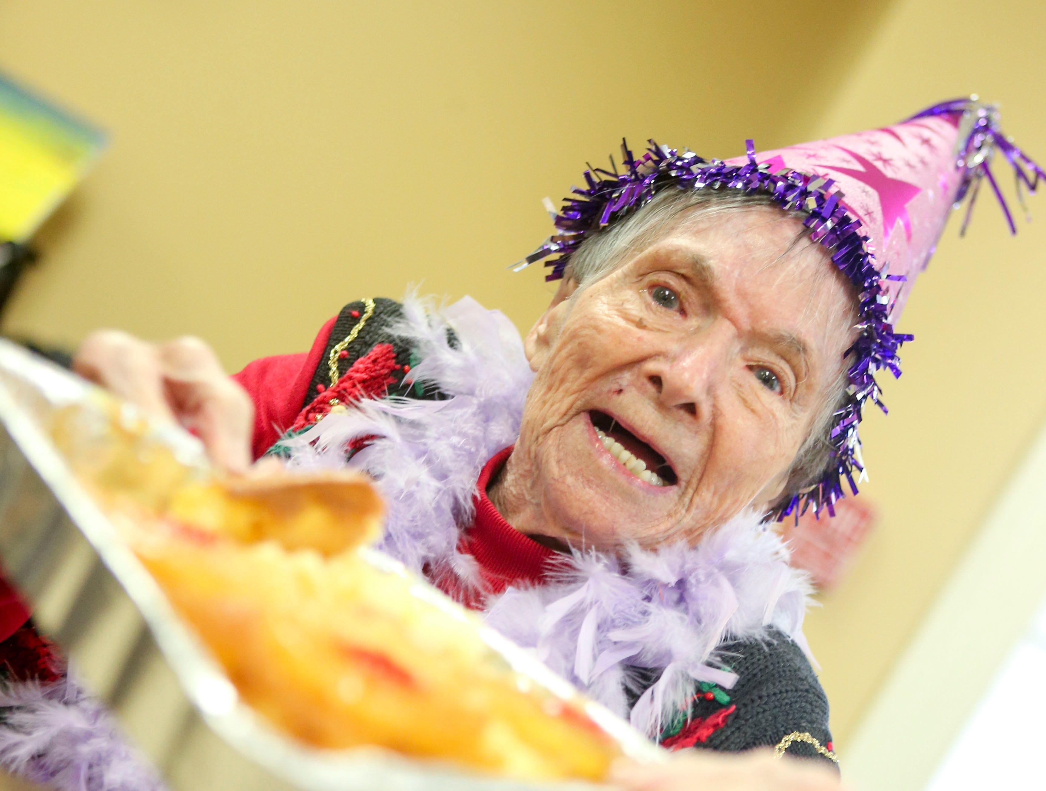 Ida Feldman proudly holds up her inside out pineapple cake made for her on her 100th birthday at Regency Retirement Home in Jackson, Tenn., on Thursday, Dec. 20, 2018.